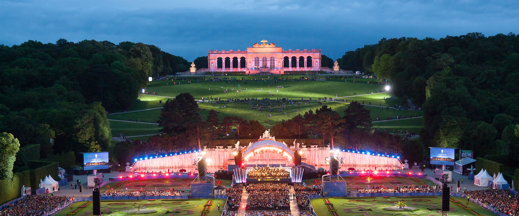outdoor evening concert with orchestra in mid-ground and large palace in background