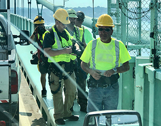 Follow the production team as they scale the bridge with the maintenance crew.