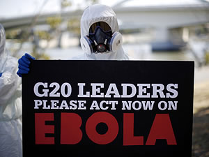 person in hazmat suit holding a sign that says 'G2 Leaders Please Act Now on Ebola'