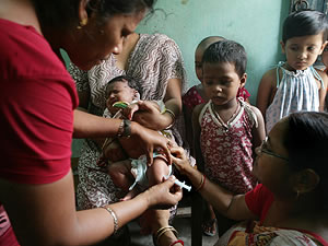 Woman administering the hepatitis B vaccine to a child at a rural health center in India