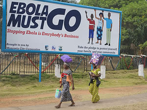 Two women walk in front of a billboard, which says 'Ebola must go. Stopping Ebola is Everybody's Business'