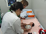 At Candido Vargas Institute in João Pessoa, Brazil, a geneticist examines an infant with microcephaly, a brain defect associated with Zika virus infection.