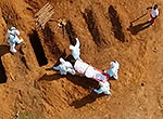 Personal protective equipment (PPE)-laden workers bury an Ebola victim at the vast Waterloo Cemetery in Sierra Leone.