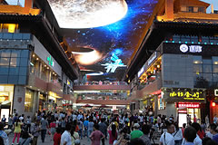 people walking in a mall with a giant LED screen overhead