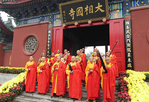 Group of Buddhist monks standing on temple steps, holding musical instruments
