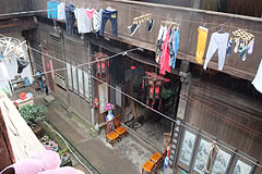 exterior view of old wooden house with laundry hanging from a line above teh front entrance