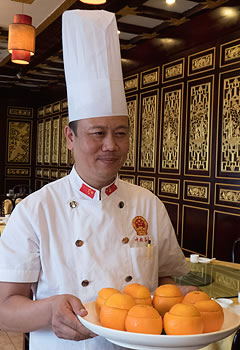 man in chef's uniform carrying a platter of cut oranges