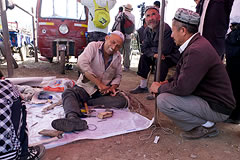 2  men crouching next to a man sitting on a blanket, working on leather belts