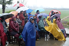 group of people wearing rain gear, watching an outdoor opera