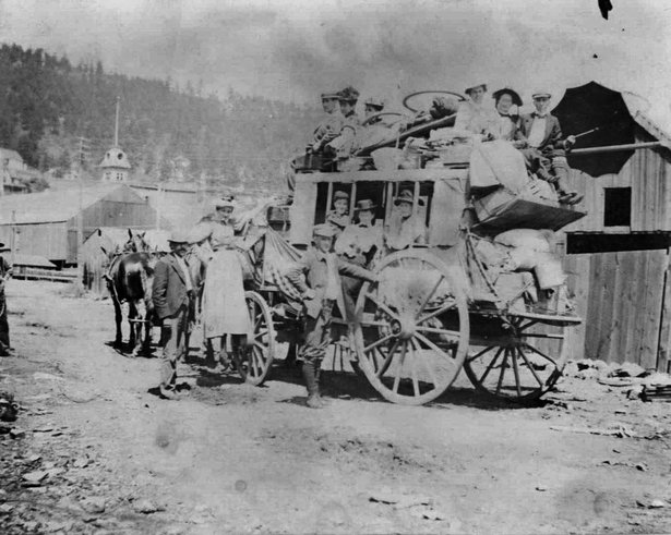 A group of men and women on a stagecoach in Deadwood, 1880s.