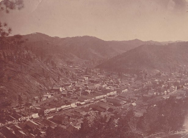 Early view of Deadwood taken from the Forest Hill neighborhood.  The view is looking down upon the business district.  From the buildings pictured, the photograph can be dated sometime between fall 1877 to fall 1879.