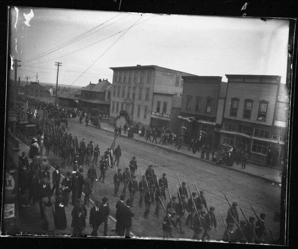 1st SD march west on 10th St. in Sioux Falls. (Rock Island Railroad Depot in background).