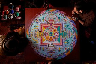 Buddhist monks put the finishing touches to a sand Mandala.