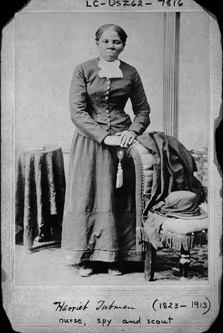 Harriet Tubman standing with hands on back of a chair.