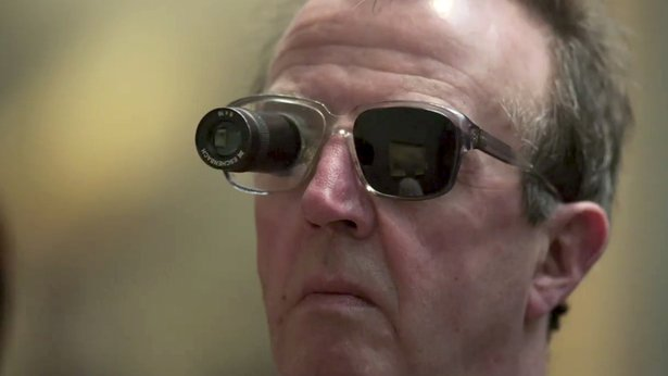 A close up of a man's facce as he looks at a painting. The man wears glasses with one lens blacked out and some kind of magnifying lens attached to the other