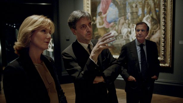 A man gestures as he discusses a painting with a woman. Another man looks on. All three are in suits.