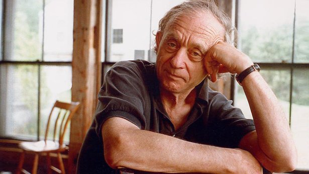 Color photo of Frederick Wiseman, from the waist up, he leans his head into one hand and rests his other arm on a surface.