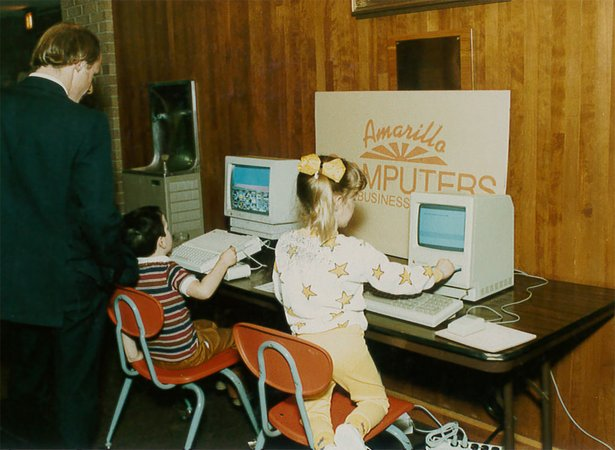 Children examine a Discovery Center exhibition about computers in the 1990s.