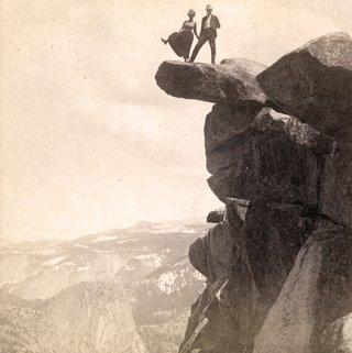 Man and woman standing atop cliff at Glacier Point in Yosemite National Park, California.