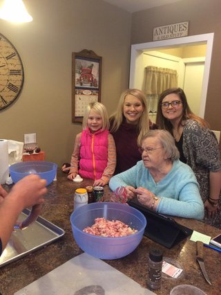 Grandma Alice works with younger generations to prepare sausage.