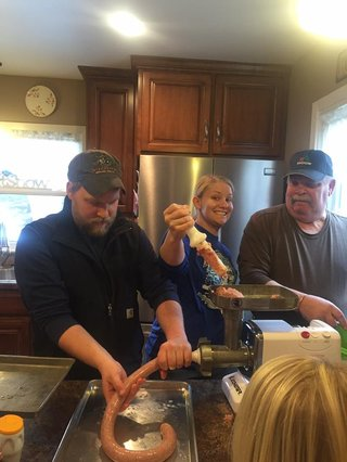 Two generations of the Kennedy family work the sausage stuffing machine.