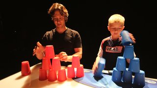 Dr. David Eagleman tries keeping up with world champion cupstacker Austin Naber, 10.