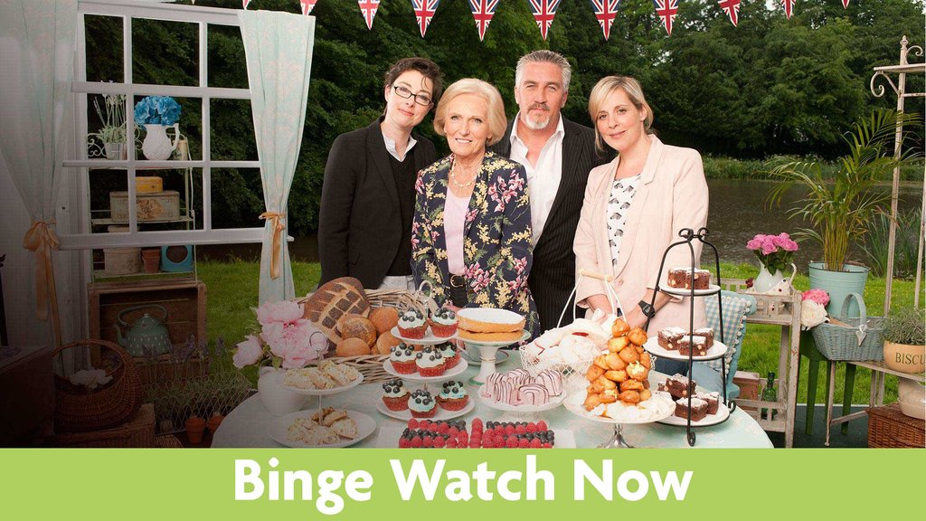 Sue Perkins, Mary Berry, Paul Hollywood and Mel Giedroyc posing behind a table of assorted baked goods.