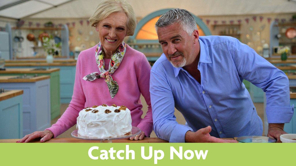 Mary Berry and Paul Hollywood pose with a cake on display on top of a wooden table.