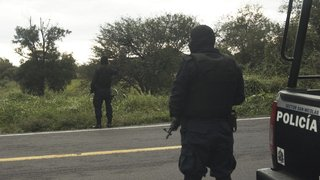 Wearing masks to conceal their identities, police investigate a dead body found in a cornfield near Juarez's home.