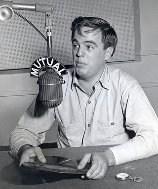 Alan Lomax seated in front of microphone