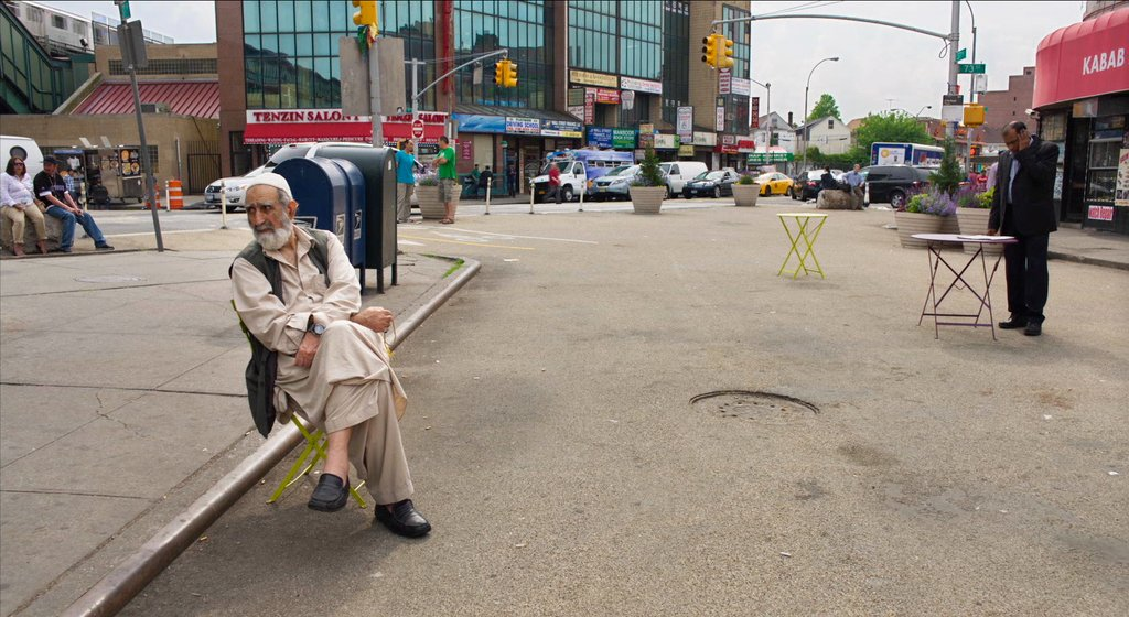 Man sits on folding chair in the street in Jackson Heights