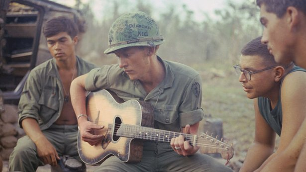 "A soldier, wearing a helmet that has ""Oklahoma Kid"" written on it, plays a guitar for a group of other soldiers."