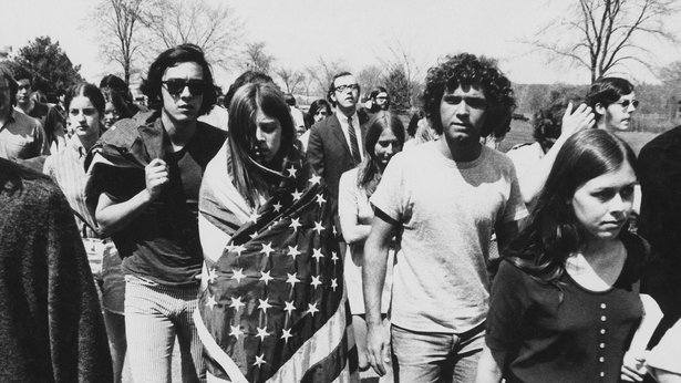 A black-and-white photo of American protesters. In the foreground, a woman is wrapped in an American flag.