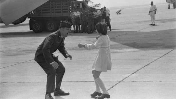 A black-and-white photo of a young girl about to embrace a male servicemember on an airfield.