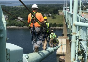 A team of maintenance workers scales alongside the bridge.